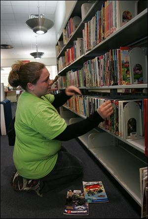 Chelsea Custer, exploring the shelves at the main library, says she must wait longer for materials to appear in the library system.