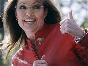 Sarah Palin flashes a thumbs up towards her husband Todd as she begins to address a crowd during a stop of the Tea Party Express on Boston Common in Boston, Wednesday,