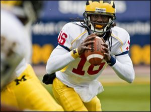 Michigan quarterback Denard Robinson threw and ran for touchdowns yesterday before 35,000 fans at the annual spring game.