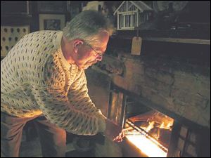 Chris Werkman takes his turn cooking the traditional steak dinner in the fireplace at the club.