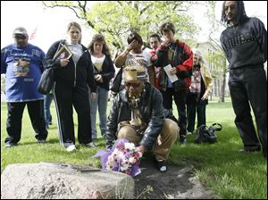 Wendy Robinson, whose son, Donnie, was murdered, lays flowers on a memorial as other family members of murder victims watch on the Lucas County Courthouse lawn. The Parents of Murdered Children and the county prosecutor's office organized the vigil last evening in observance of Victims' Rights Week.