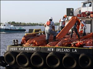Workers load a vessel to help contain oil leaking from last week's oil rig explosion in the Gulf of Mexico. Officials raised leak estimates to 5,000 barrels, or 200,000 gallons, of oil a day.