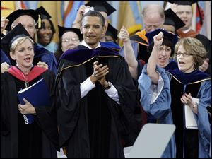 "President Barack Obama applaudes as Michigan Gov. Jennifer Granholm, left, and UM President Mary Sue Coleman, right, sing ""The Victors"" during the commencement ceremony."