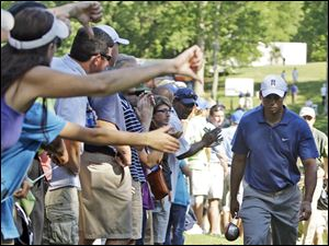 Fans give Tiger Woods a thumbs down as he leaves the 15th hole during the second round of the Quail Hollow Championship in Charlotte Friday.