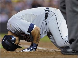 Detroit's Gerald Laird collapses in pain after fouling a ball off his left shin in the fifth inning.