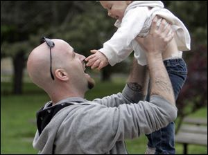 Former Marine Eric Bartkowiak of Toledo, playing with his daughter Lillie, 2, is among the veterans who have been assisted by Arms Forces.