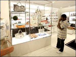 Prices at high-end handbag maker Coach Inc., operator of this store in Dallas, are 12 percent lower than a year ago. But the company told investors it might raise prices this year as sales rebound.