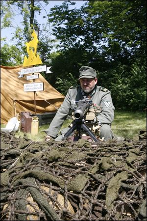 Toledoan Mark Pacholski, portraying a member of the German Gebirgsjager, or mountain infantry, watches the enemy from behind barbed wire and sandbags.