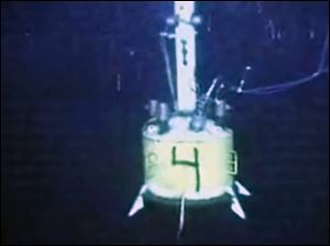 A capping device hangs in the water at the site of the Deepwater Horizon oil spill on Thursday, in this image made from video made available by British Petroleum (BP PLC).