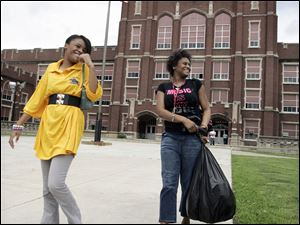 Na'Risa Washington, left, and her sister, Na-Reze, leave Libbey High School, which closes for good,  after taking their final exams yesterday. Na'Risa says she hopes to attend Bowsher next year.