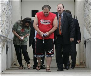 Amera Akl, left, and Hor Akl are escorted from the federal courthouse in Toledo by U.S. Marshals. The Akls will be detained until a hearing Tuesday. Their children are in the care of relatives.