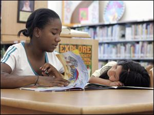 Tyreonna McCulley, 12, reads to Ruth Alonso, 6, at the Toledo Boys and Girls Clubs program at Sherman Elementary School.