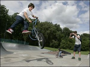 Zak Karnowski, 16, performs a slick trick while his friend James Dickens, 15, captures it on video at the skate park in Highland Park in South Toledo. 