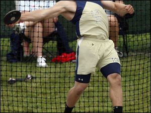 St. John's Cody Riffle has both feet of the ground as he sends discus flying in winning effort.