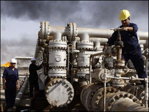 Iraqi workers are seen at the Rumaila oil refinery, near the city of Basra, Iraq, in this Dec. 13, 2009 file photo.