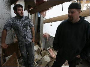 David Northam, left, and his friend Robert J. Rudat assess the damage to Mr. Northam's future father-in-law's apartment on Dennison Road, site of some of the worst devastation in Dundee.