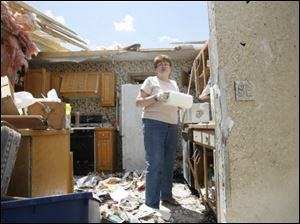 Shirley White sorts through belongings in her destroyed home. She clung to a bathroom sink as the storm tore the house apart.