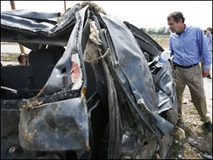 U.S. Sen. Sherrod Brown (D., Ohio) looks at the wreckage the tornado left behind.
