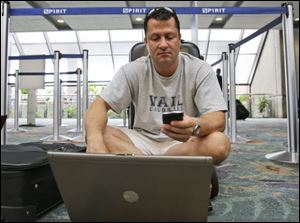 Doug Ferraro, of St. Petersburg, Fla., checks his phone for messages as he sits on the floor at the Spirit Airlines counter as his birthday-vacation flight to Nassau was canceled at Fort Lauderdale-Hollywood International Airport in Fort Lauderdale, Fla..