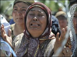 An Uzbek woman who says she fled from the southern Kyrgyz city of Osh after her family was killed weeps Monday as she stands in line in no-man's-land near the Uzbek village of Jalal-Kuduk waiting for permission to cross into Uzbekistan.