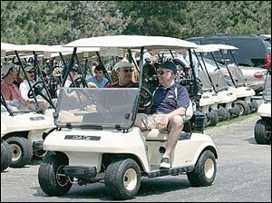 Golfers head to the first hole during the University of Toledo College of Medicine golf outing at Toledo Country Club.