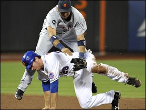 Tigers second-baseman Carlos Guillen tumbles over Mets Ike Davis after forcing out Davis in the 6th inning of the game at the Gotham City.