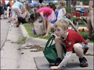 Joshua Fellman, 9, of Lambertville, bends to retrieve some of the candy distributed during the parade.