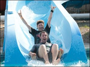 Adam Sandler, foreground, and David Spade barrel down a water slide in a scene from 'Grown Ups.'