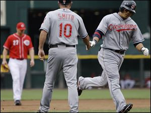 The Indians' Shin-Soo Choo is congratulated by third base coach Steve Smith after hitting his first of two home runs.