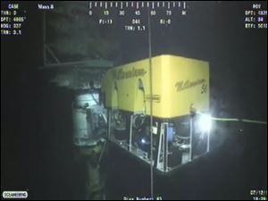 In this image taken from video provided by BP PLC, a new containment cap is lowered over the broken wellhead Monday at the site of the Deepwater Horizon oil spill in the Gulf of Mexico.