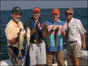 Blade outdoors editor Steve Pollock, from left, ODNR director Sean Logan, Gov. Ted Strickland and charter captain Paul Pacholski show off their day's catch.