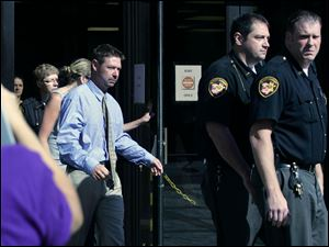 Eric Skowron is escorted out of Toledo Municipal Court by deputy sheriff personnel after his arraignment for shooting Tyson.
