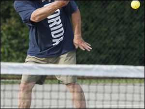 Jeff Foster aims the ball over the net. Pickleball games go to 11 points.