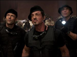 Jason Statham, from left, Sylvester Stallone and Randy Couture appear in a scene from 'The Expendables.'