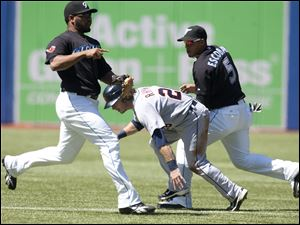 Detroit's Will Rhymes, center, is caught between Toronto's Edwin Encarnacion, left, and Yunel Escobar in the first inning.