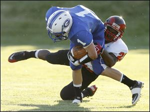 Anthony Wayne's Matt Granger, who rushed for 86 yards and a touchdown,is brought down by Antwon Dupree of Rogers.