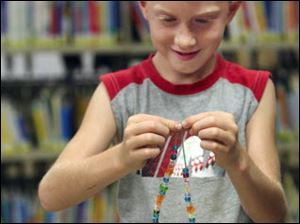 Zach Murdock, 6, of Petersburg puts the finishing touches on a necklace.