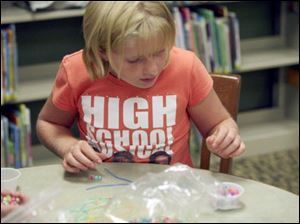 Meg Murdock, 9, of Petersburg finds some beads to string together.
