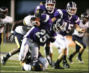 Fremont Ross' Tylor Trautwein, center, is brought down by Whitmer's Nick Wert during Friday night's game won by the Little Giants.<br>