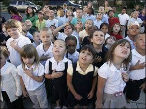 CTY remember11p  9/10/10  The Blade/Dave Zapotosky Students at Navarre Elementary School in East Toledo watch as the U.S. flag is raised in front of their school during a ceremony to remember the terrorist attacks of September 11, 2001, Friday Spetember 10, 2010.  Kindergarten students from front row left, include Karissa Santillo, Brittney Engelhardt, Justice Clark, Jewel Martinez, and Alyssa Slater.   A moment of silence was observed and essays were read by two sixth grade students, Paul Espino, and Locadio Ruiz.  Summary:  9/11 observation at Navarre Elementary School.