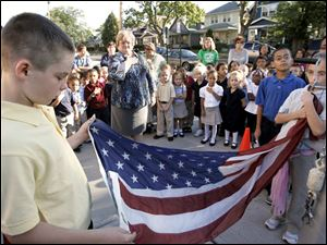 CTY remember11p  9/10/10  The Blade/Dave Zapotosky John Martis, 11, left, and Charlene Palmer, 11, right, raise the U.S. flag as students and staff at Navarre Elementary School in East Toledo hold a brief ceremony to remember the terrorist attacks of September 11, 2001, Friday September 10, 2010.  Both are sixth grade students. A moment of silence was observed and essays were read by two sixth grade students, Paul Espino, and Locadio Ruiz. Summary:  9/11 observation at Navarre Elementary School.
