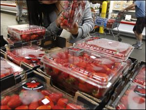 A Costco customer checks strawberries at a store in California.