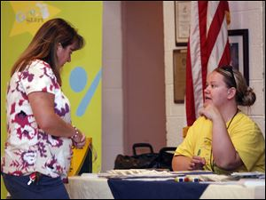 Kim Betway, left, of Monroe gets information about child safety from Amy Zarend of the Great Start Collaborative of Monroe during the Nevaeh Buchanan event at the Moose Lodge.