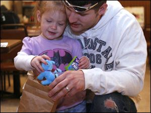 Dion Elmore and daughter Alexis, 2�, look through a goody bag she received at the event. Mr. Elmore helped search for Nevaeh.