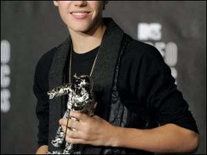Teen pop sensation Justin Bieber smiles with his award for best new artist.
