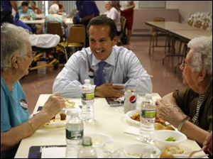 Providence, R.I. Mayor and Democratic Congressional candidate David Cicilline, center, talks with Louise Pasacane, left, and Violet Champagne, both from Woonsocket, R.I., during a pasta dinner at an elderly care facility.