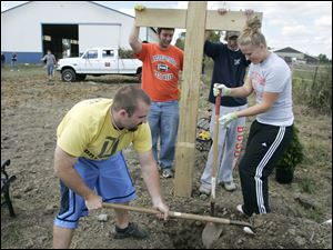 Bowling Green State University students, from left, Alex Binger, Tyler Strittmatter, Mike Krafft, and Anne Yenrick set up a cross at Serenity Farm near Luckey.