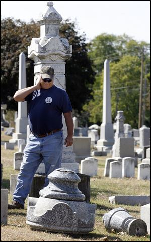Roy Wise surveys damage at McPherson Cemetery in Clyde after vandals struck. Cemetery crews have begun repairing or resetting almost 200 markers.