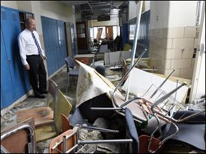 Jim Witt surveys a hallway in the school that was ripped apart by the June tornado. He said he often felt disbelief that the insurance company said the building was salvageable.