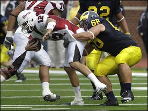 Michigan defensive tackle Mike Martin sacks Massachusetts quarterback Kyle Havens in the second quarter of Saturday's game at Michigan Stadium.